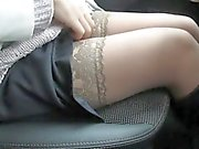 Touching her legs in stockings in a car