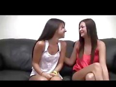 Two brunette lesbian babes chat on the couch before playing with each other