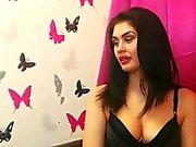 Curvaceous brunette beauty in a low-cut black top flaunts h