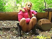 Squatted girl peeing in the autumn park