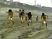 Naked women race across the beach with a ball between their