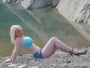 Busty blonde displays her figure near the lake