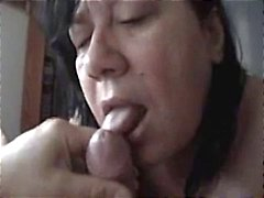 Chubby mature swallows his cock and licks his feet too and gets a facial