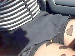 Ragazza sexy in minigonna e scarpe col tacco in auto