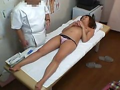 Foxy Asian gal lies on the table for the doctor to check ou